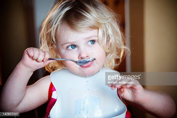 Young girl eating with spoon