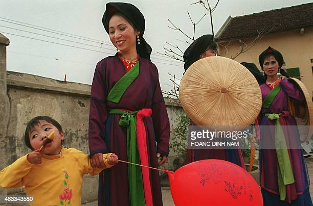 A young girl eats an ice beside singers of 'quan ho' in traditional dresses in Northern province of Bac Ninh where an annual threeday spring song...