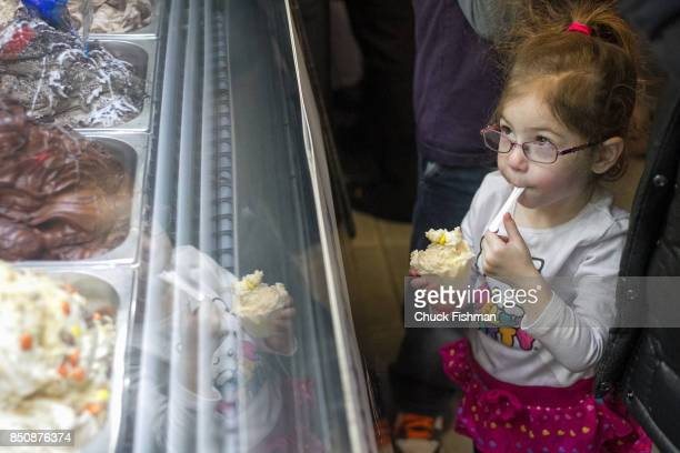 A young girl eats ice cream as she looks into a glass display case during the Chocolate Expo at the Cradle of Aviation museum Garden City New York...