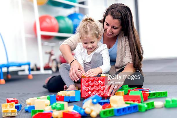 Young girl enjoying a therapy exercise with help