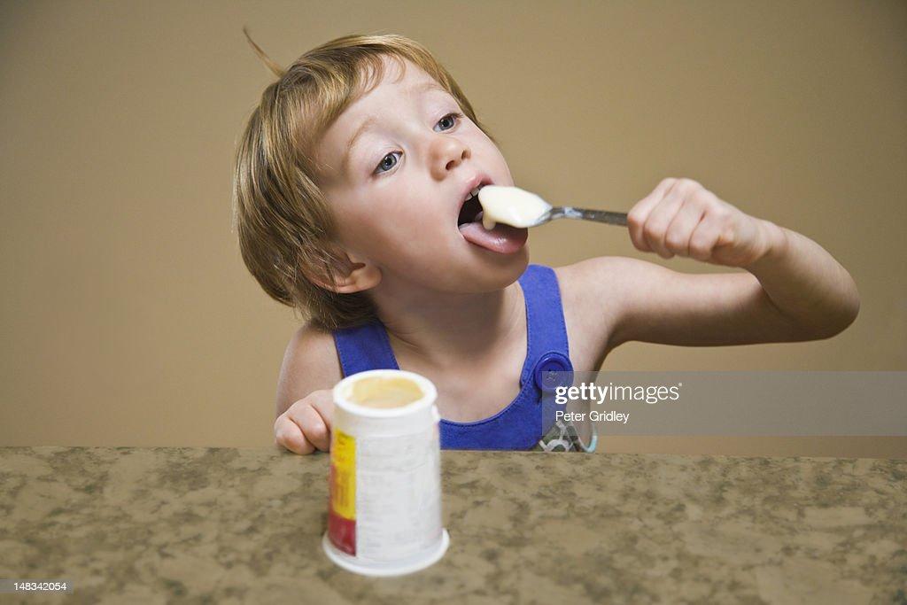 Young girl enjoying eating a yogurt : Stock Photo