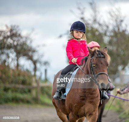 Young girl enjoying horse riding lesson