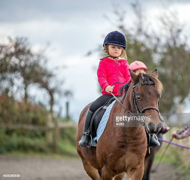 Young girl enjoying horse riding lesson