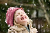 Young girl enjoying snow falling on her face