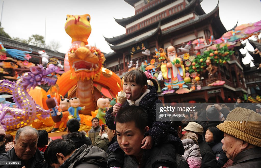 A young girl enjoys an ice-cream during the Lunar New Year holiday in Shanghai on February 12, 2013. The Lunar New Year typically marks the largest annual movement of people as millions of people across China and other Asian countries squeeze into packed trains and buses to journey home to spend the season with their families. AFP PHOTO/Peter PARKS