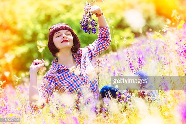Young girl enjoys in flourishing field of solar