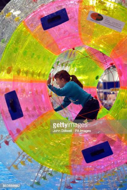 A young girl enjoys rotating on water inside a giant inflatable tube on the first day of the London Boat show 2014 at the ExcCel centre Docklands in...