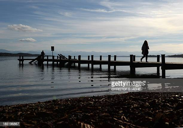 A young girl enjoys the sunny autumn weather on a pier on the lake Starnberger See southern Germany on October 18 2013 Meteorologists forecast sunny...
