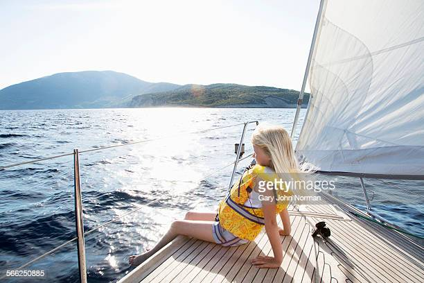 Young girl enjoys wind in her hair on yacht.