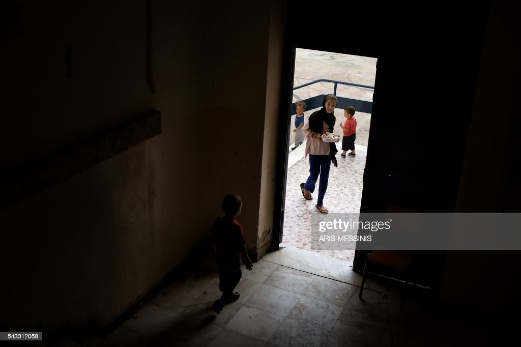 A young girl enters an abandoned school used by volunteers for hosting families of refugeees from Syria and Afghanistan in Athens on June 27, 2016. / AFP / ARIS