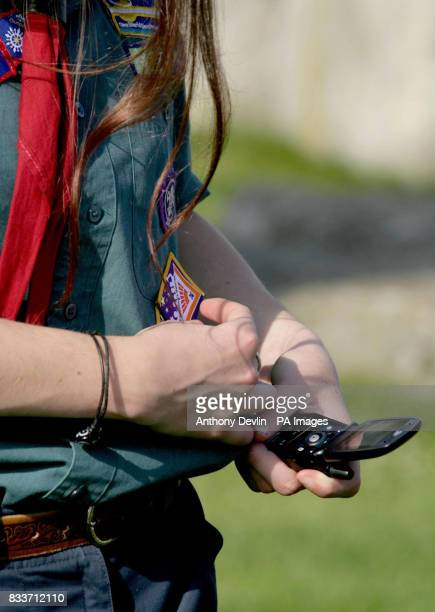 A young girl examines her new badge as hundreds of Scouts renew their Scout Promise at Stonehenge in Wiltshire to celebrate Scouting's centenary