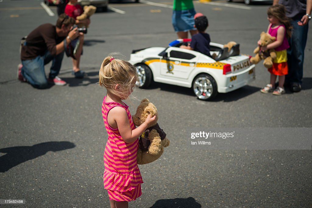 A young girl examines the teddy bear that was given to her by the police, on July 14, 2013 in Lac-Megantic, Quebec, Canada. A train derailed and exploded into a massive fire that flattened dozens of buildings in the town's historic district, leaving 60 people dead or missing in the early morning hours of July 6.