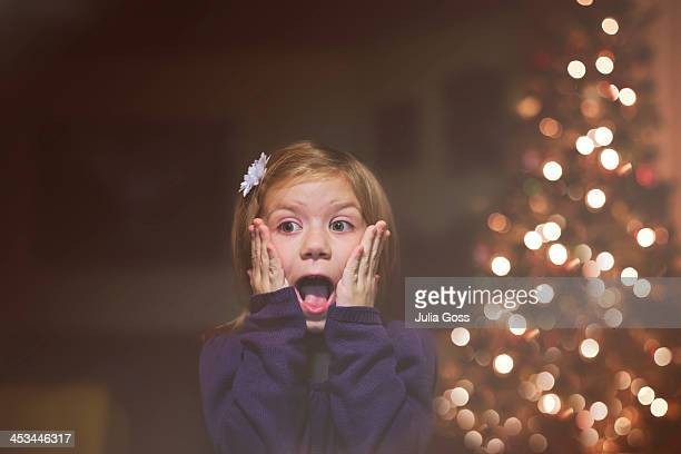 Young girl excited infront Christmas tree