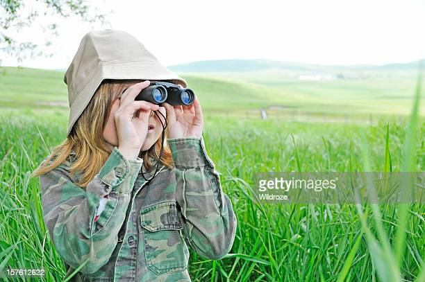 Young girl explores nature with binoculars
