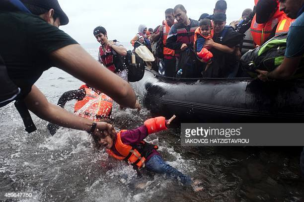 A young girl falls in the water as migrants and refugees land on the beach at Sykamia west of the port of Mytilene on the Greek island of Lesbos...