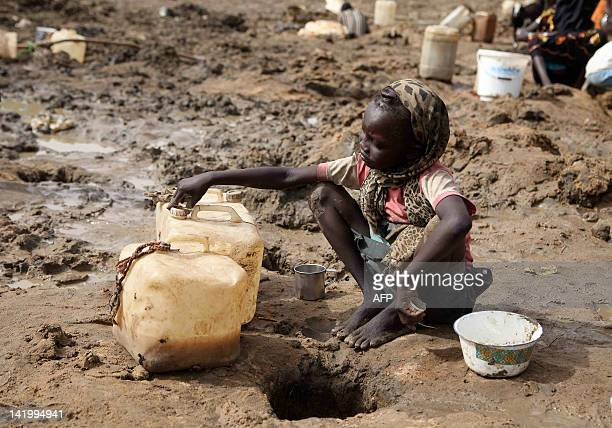 A young girl fetches murky water on March 22 2012 from a hole dug near a dried well in Jamam South Sudan where chronic water shortages for some 35000...