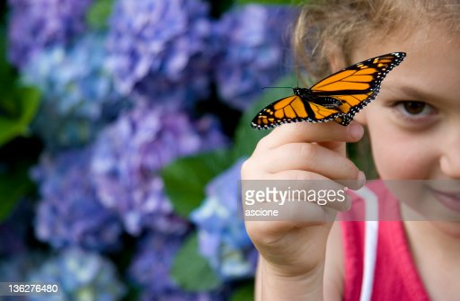 Young girl finding beauty in monarch butterfly on her finger