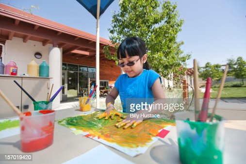 Young girl (age 3-4) finger painting at school : Stock Photo