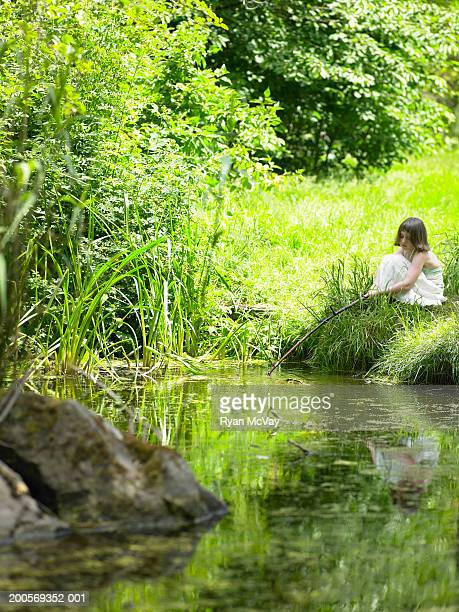 Young girl (6-7) fishing in stream on edge of forest