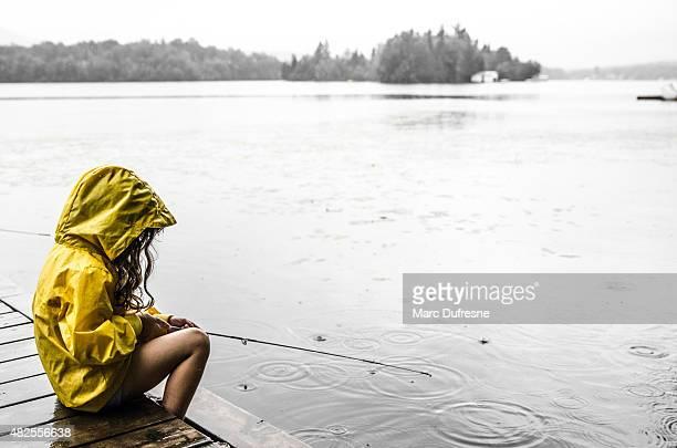 Young girl fishing under rain