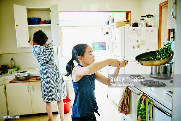Young girl flipping green beans in pan on stove