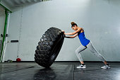 Side view of young woman picking up tractor tire in the gym