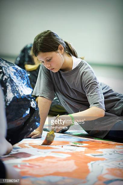 Young girl focusing on painting a mural on the floor