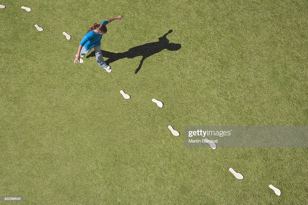 Young girl following footprints on grass