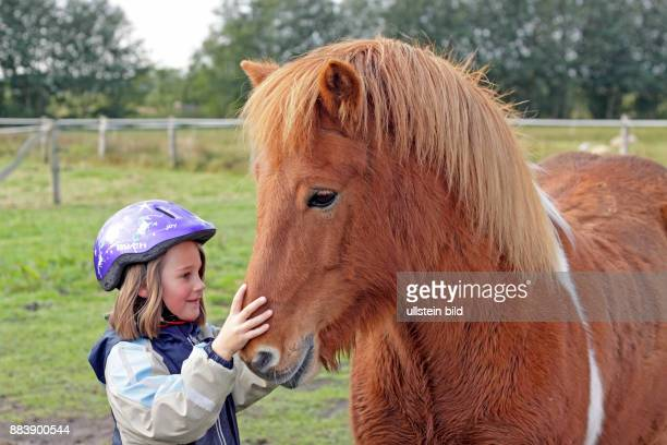 young girl fondling a pony