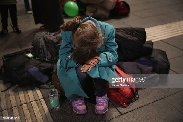 A young girl from Syria sits on luggage as she and her family waited on a railway platform at Salzburg Hauptbahnhof railway station in the hope of...
