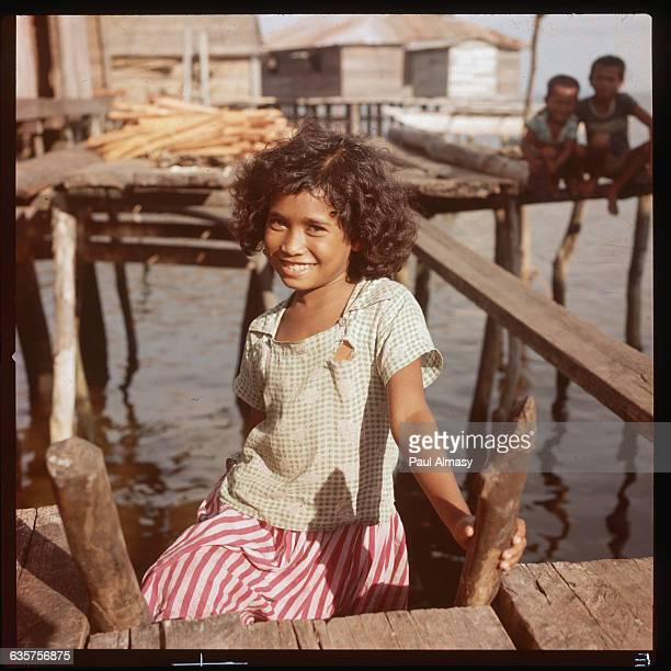 A young girl from the Moro tribe stands on a ladder near her house The houses are constructed on piles over water on the exterior of Mindanao Island...