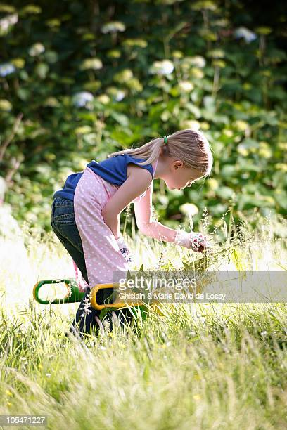 Young girl gardening with gloves and apron