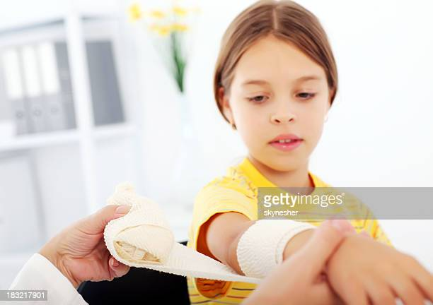 Young girl getting a bandage on her arm in hospital.