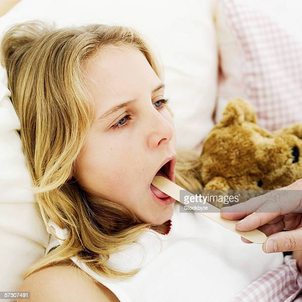 Young girl (12-14) getting her throat checked with a tongue depressor