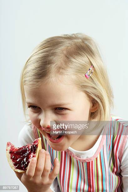 A young girl giggling while eating a bread and jam