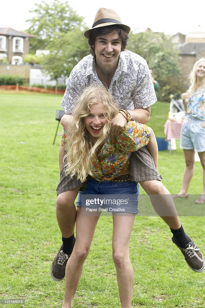 Young girl giving her boyfriend a piggy back : Stock Photo