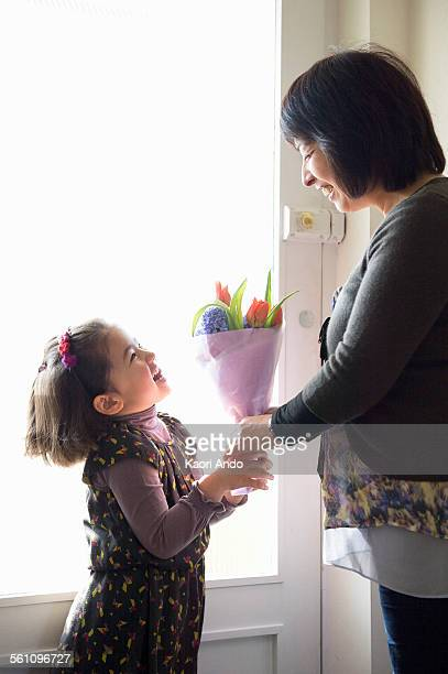 Young girl giving mother flowers