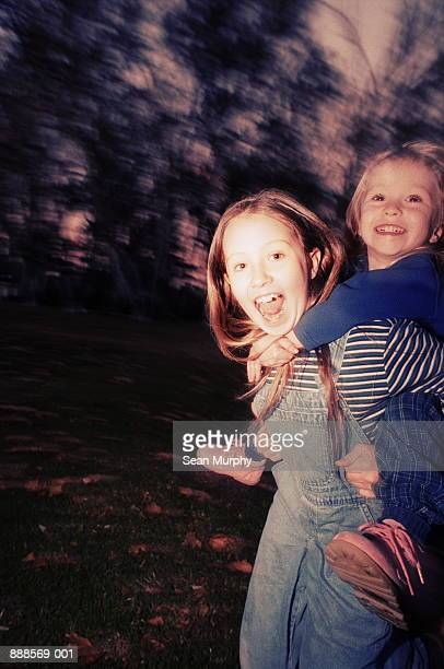 Young girl (9-10) giving sister (4-5) piggyback ride (blurred)