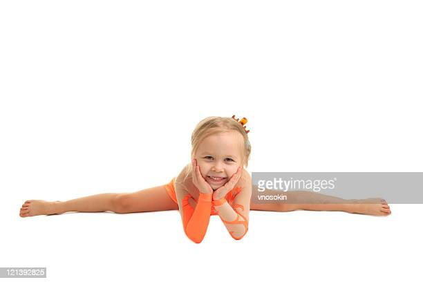 A young girl gymnast in a straddle split holding her face