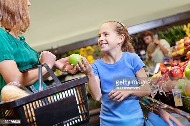Young girl handing apple to mother while shopping for groceries