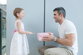 Young girl handing present to her father