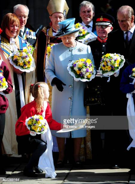 A young girl hands back Queen Elizabeth II's order of service after she dropped it following the Royal Maundy Service outside Derby Cathedral