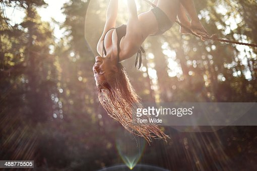 Young girl hanging upside down from a rope