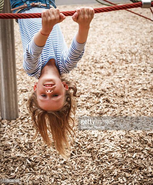 Young girl hanging upside down