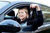 Girl sitting in her car and showing key