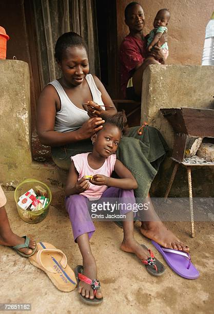 A young girl has her hair brushed by her mother in Wilberforce on November 26 2006 in Freetown Sierra Leone Sierra Leone was ravaged by a decade long...