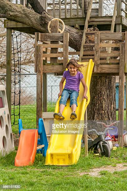 Young girl having fun on slide attached to a tree house