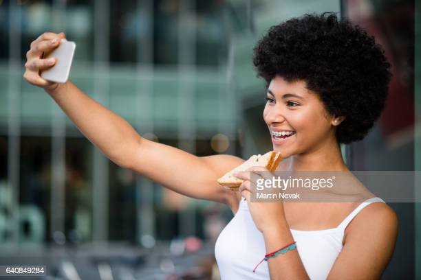 Young girl having fun outdoors. Taking selfie while eating sandwich.