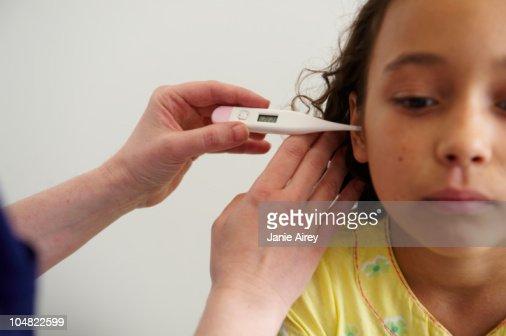 Young girl having temperature taken