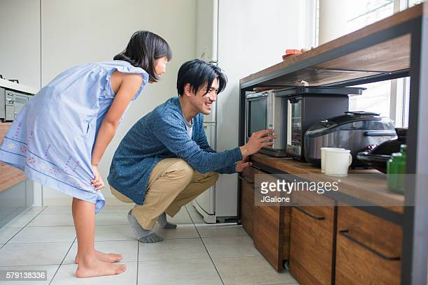 Young girl helping father in the kitchen
